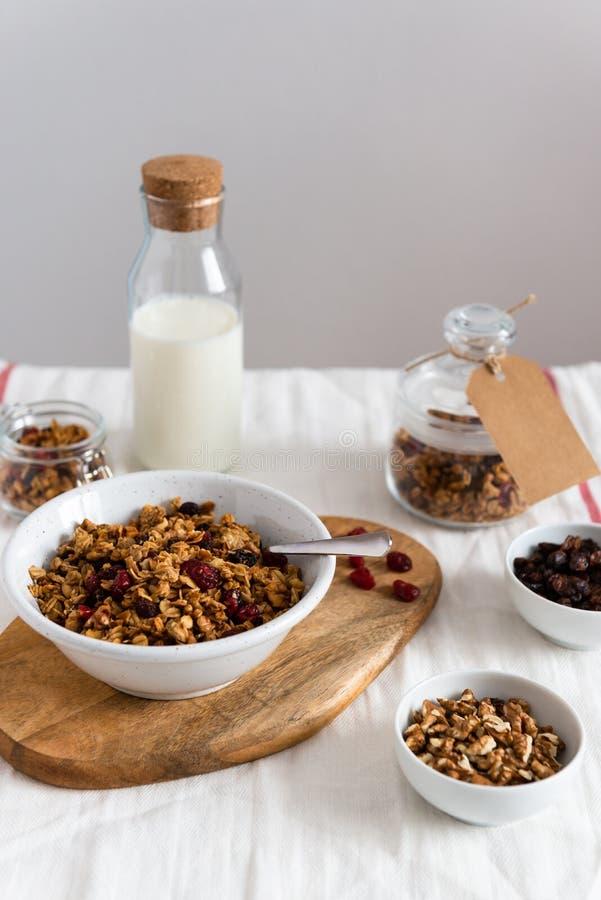 Kom van eigengemaakte granola met noten en vruchten, fles melk op witte linnenachtergrond Zijaanzicht, exemplaarruimte Gezond Ont stock afbeeldingen