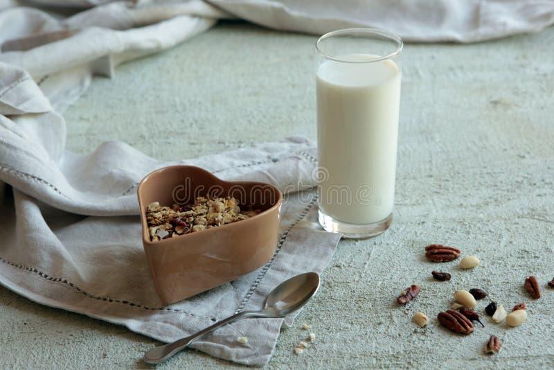 Kom van eigengemaakte muesli met noten, bessen, droge vruchten, glas melk en honing Gezond Ontbijt stock foto's