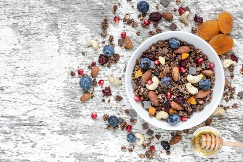 Kom van granola of muesli van de chocoladehaver met noten, bessen, droge vruchten en honing royalty-vrije stock afbeeldingen