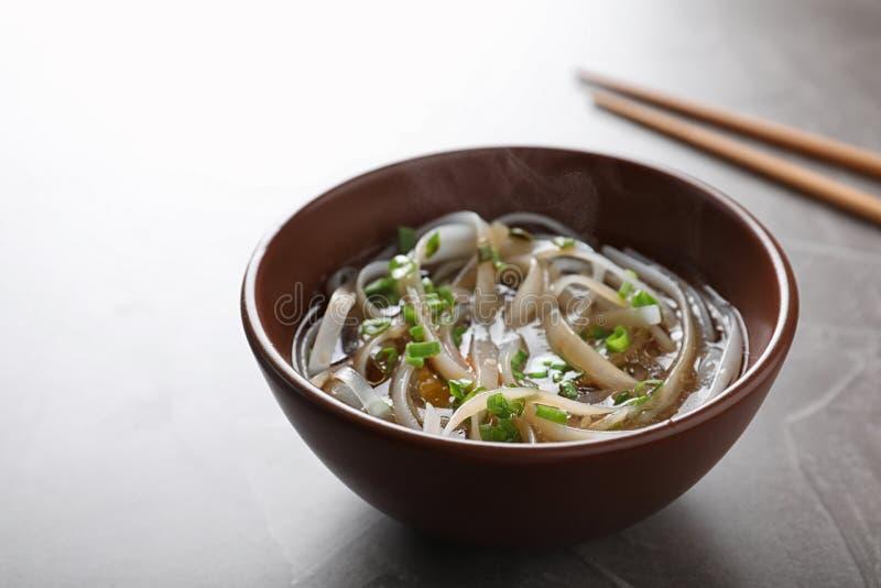 Kom van heerlijke rijstnoedels met bouillon en kruid stock afbeeldingen