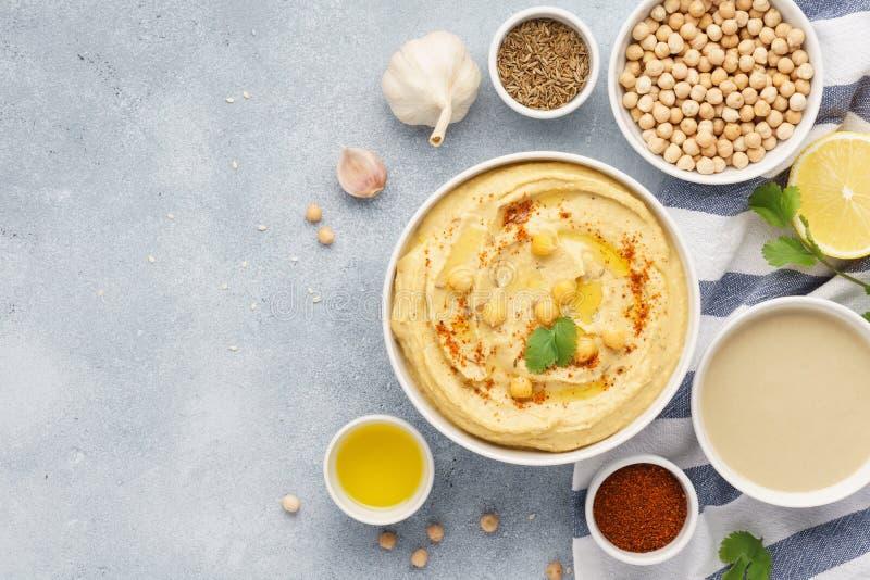 Kom van hummus en ingrediënten voor het koken stock foto
