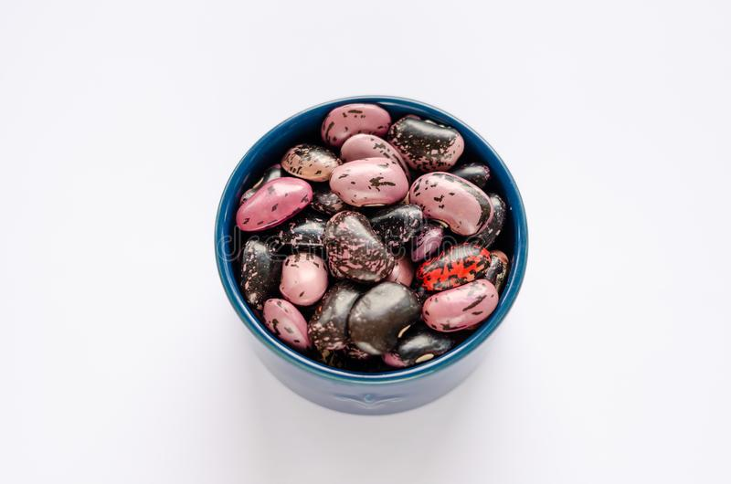 Kom van multi-colored droge bonen op witte achtergrond stock foto's