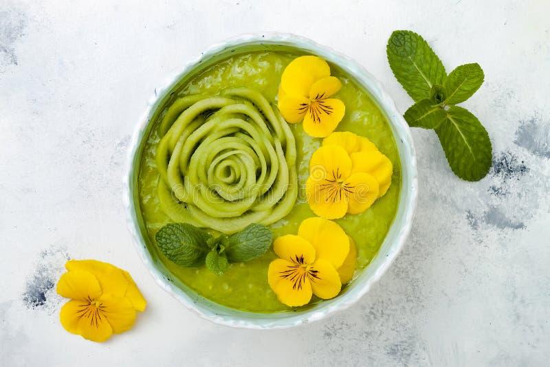 Kom van ontbijt detox nam de groene die smoothie met kiwi wordt bedekt en eetbare Viooltjebloemen toe stock afbeelding
