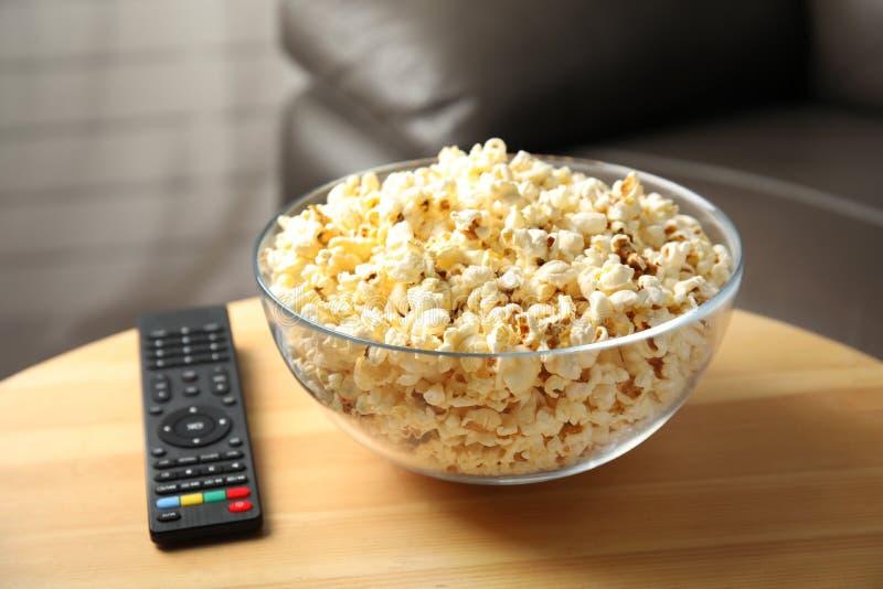 Kom van popcorn en TV ver op lijst royalty-vrije stock fotografie