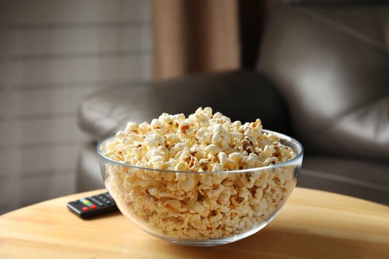 Kom van popcorn en TV ver op lijst stock foto's