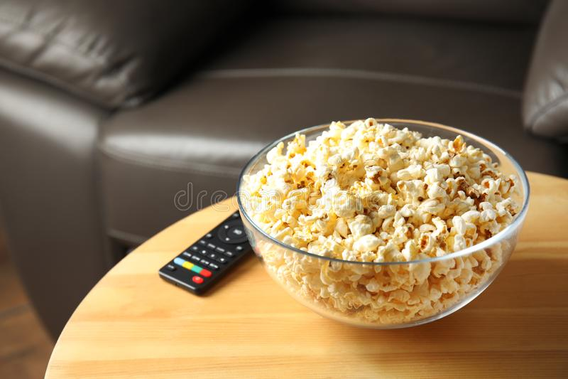 Kom van popcorn en TV ver op lijst stock fotografie