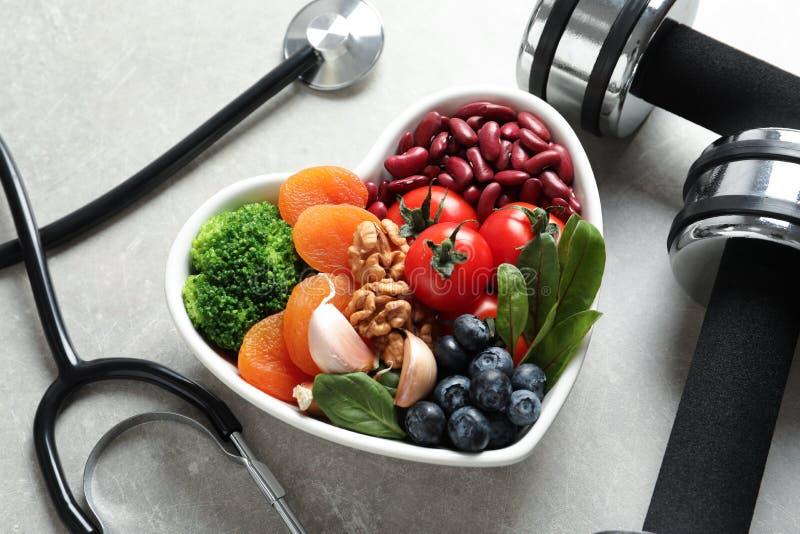 Kom van producten voor hart-gezonde dieet, domoren en stethoscoop stock foto