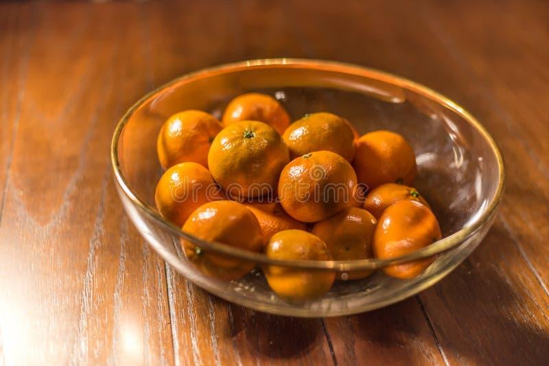 Kom van sinaasappelen op houten lijst stock foto