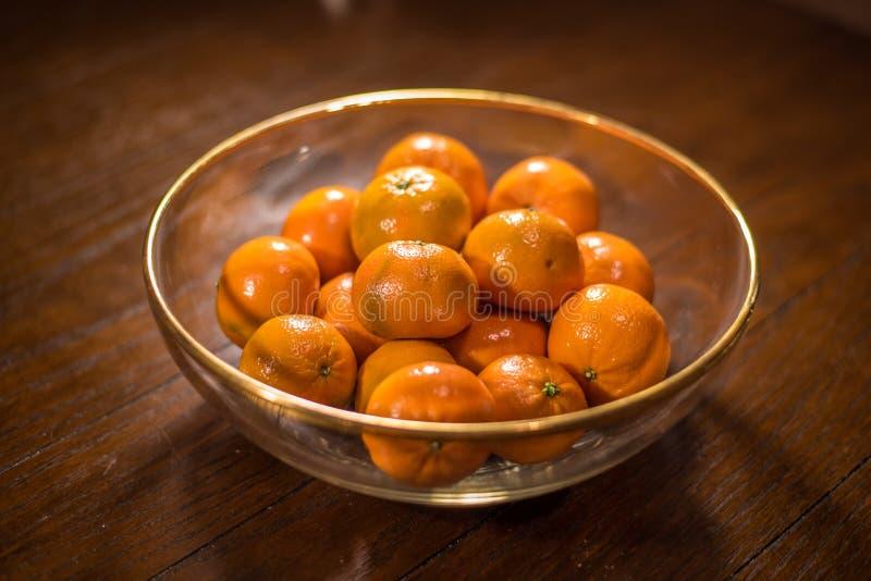 Kom van sinaasappelen op houten lijst stock fotografie