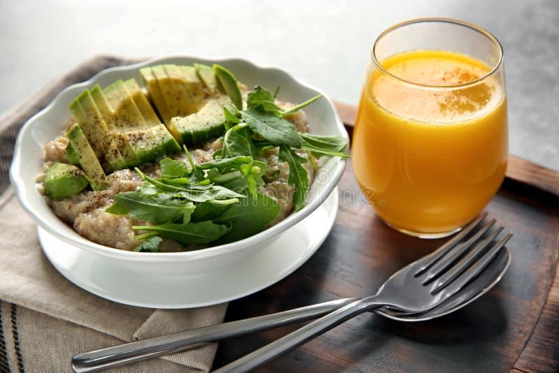 Kom van smakelijk havermeel met gesneden avocado, arugula en glas jus d'orange op houten raad royalty-vrije stock foto's