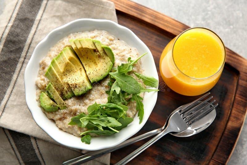 Kom van smakelijk havermeel met gesneden avocado, arugula en glas jus d'orange op houten raad stock afbeelding