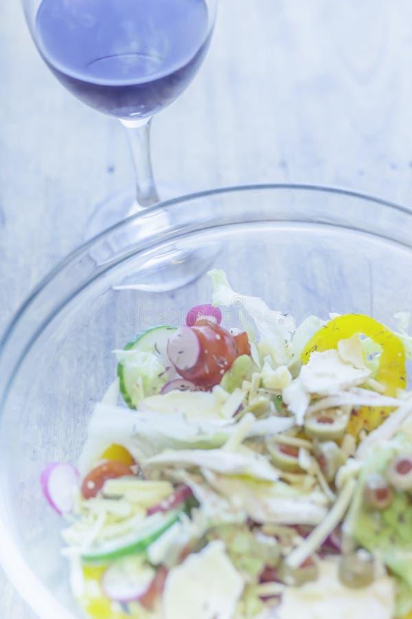 Kom verse kaas plantaardige salade en glas rode die wijn op houten lijst wordt geplaatst Vlak lay-outbeeld met blauwe tonen royalty-vrije stock afbeelding