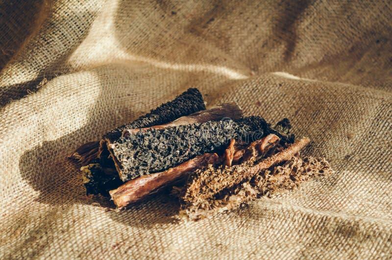 Komage för torkat nötkött Fester f?r hundkappl?pning Pinnar ligger på en säckväv Selektivt fokusera royaltyfri foto
