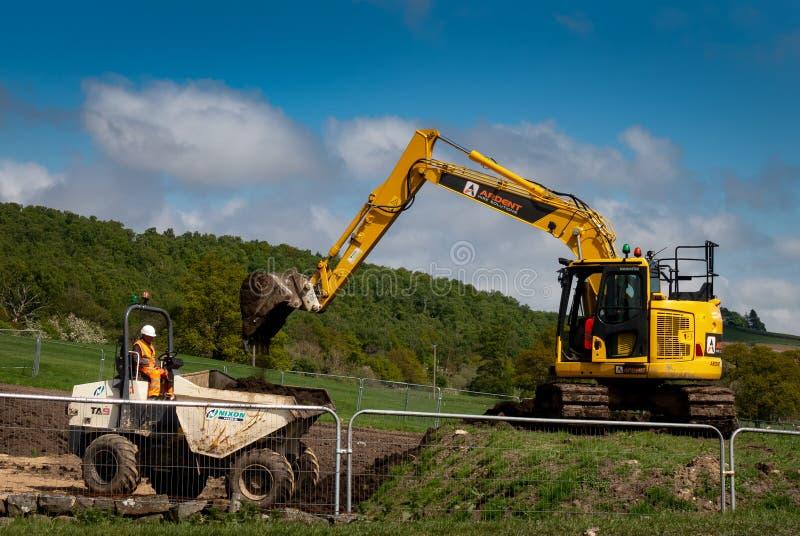 Komatsu excavator shovelling soil into a dumper stock image