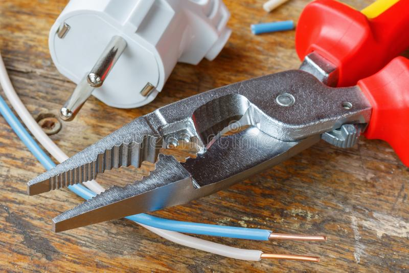Kombinacja cążki dla depeszować z elektryczną prymką i miedzianymi drutami w warsztacie na drewnianym stole obraz stock