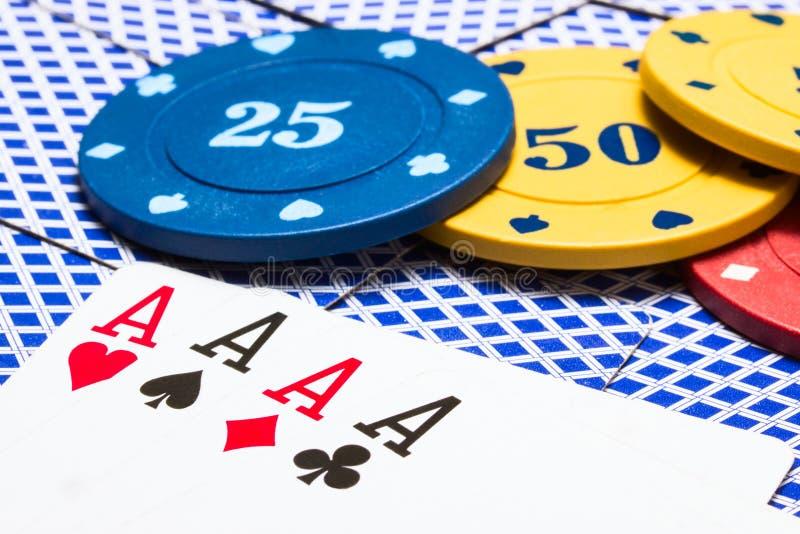 Kombination av fyra överdängare och ljusa mång- kulöra pokerchiper royaltyfri foto