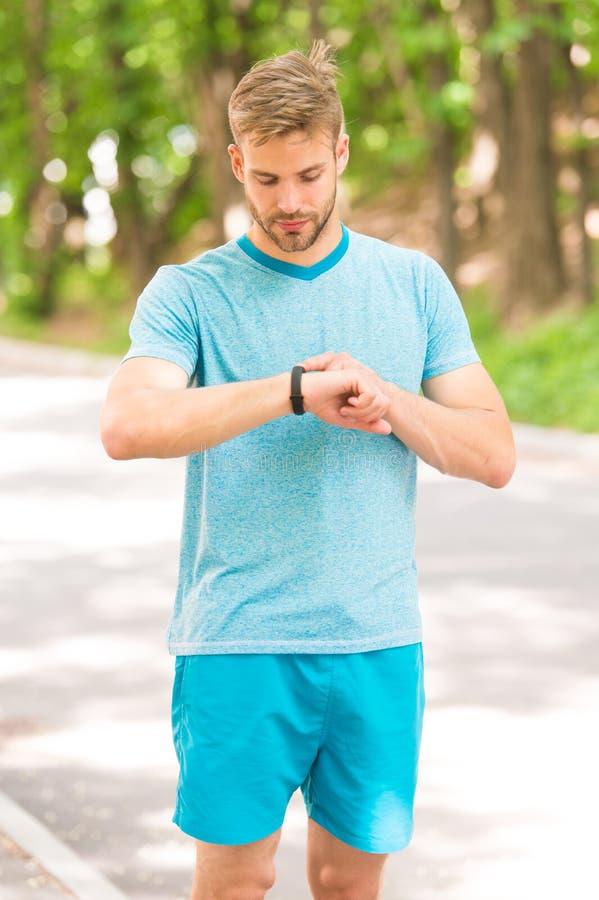 Kombination av teknologi med stil Den färdiga mannen som spårar hans kapacitet med sportar, håller ögonen på teknologi Stiligt an royaltyfri fotografi