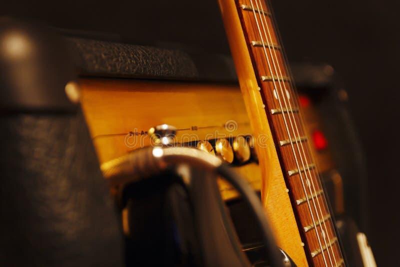 Kombinierter Verstärker für Gitarre mit klassischer E-Gitarre auf schwarzem Hintergrund Flache Schärfentiefe, zurückhaltendes, na lizenzfreies stockbild