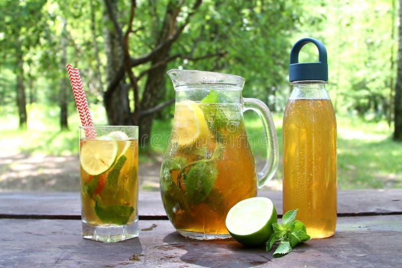 Kombucha-Tee gor Supernahrung im Glas, Krug und Flasche mit Minze und Zitrone, kalken auf dem Holztisch, im Freien lizenzfreies stockbild