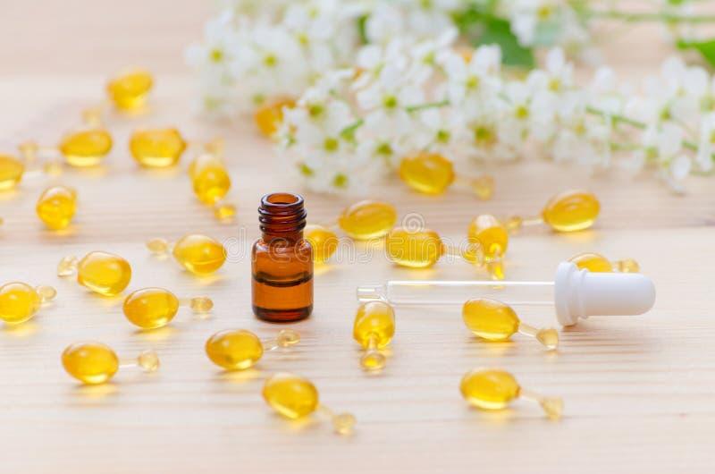 Komen de bruine fles van één ml met nerolietherische oliën, een pipet, gouden capsules van natuurlijk schoonheidsmiddel en de blo stock afbeelding