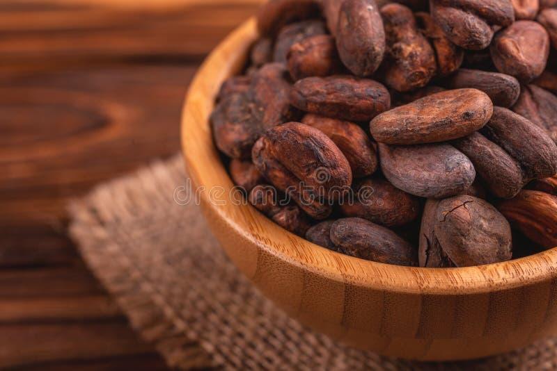 Komhoogtepunt van aromatische ruwe cacaobonen met juteservet stock afbeeldingen