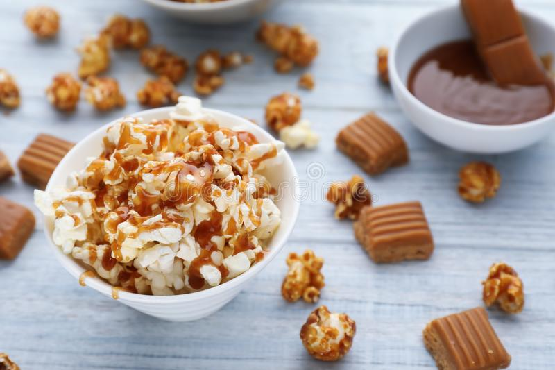Komhoogtepunt van heerlijke popcorn met karamel op houten achtergrond stock afbeeldingen