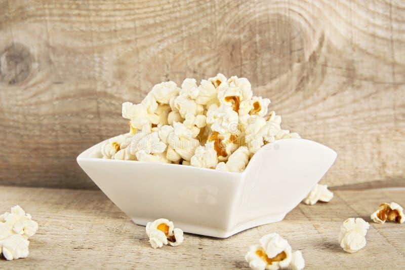 Komhoogtepunt van popcorn op houten achtergrond royalty-vrije stock afbeelding