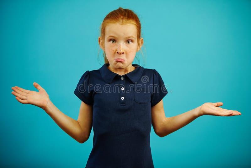 Komiczna dziewczyna z piegami i czerwonym włosy wyraża zaintrygowanie lub ignorancja, podnosząca ona ramiona, rozprzestrzenia ręk fotografia royalty free