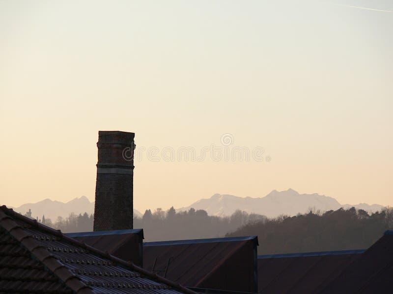 Komin stary zaniechany przemysłowy kompleks Praca przemysłowa archeologia W tle profil gór Alps zdjęcie stock