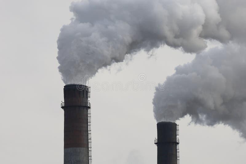 Kominy fabryczne palące z gęstym dymem Zanieczyszczenie przemysłowe powietrza, emisje z elektrowni, proble ekologii środowiska fotografia royalty free