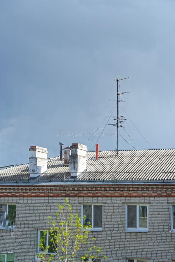Kominy i telewizyjna antena na dachu mieszkanie dom przeciw chmurnemu niebu zdjęcia stock