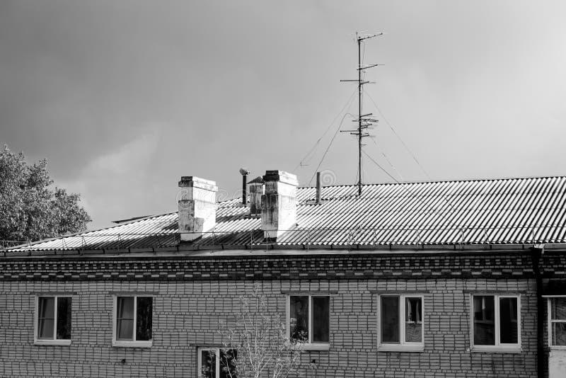 Kominy i telewizyjna antena na dachu mieszkanie dom przeciw chmurnemu niebu na, Rosja obrazy stock
