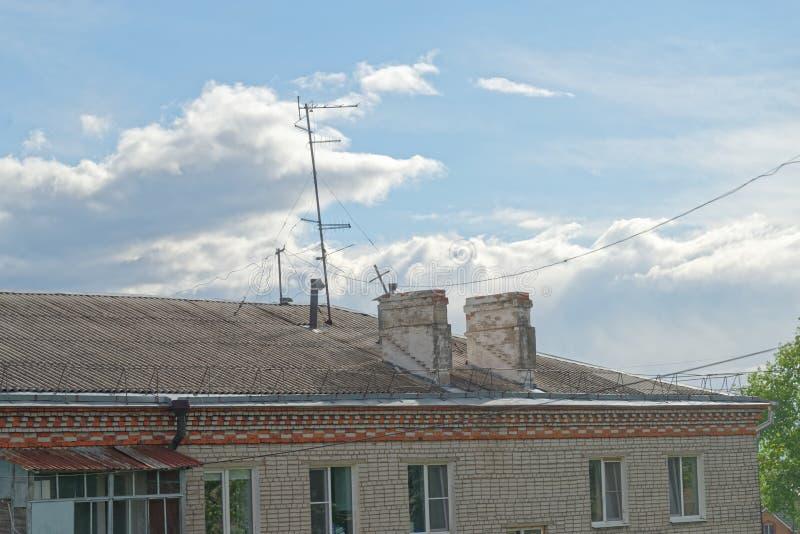 Kominy i telewizyjna antena na dachu mieszkanie dom przeciw zadziwiającemu chmurnemu niebu na, Rosja Komsomolsk-o obraz stock