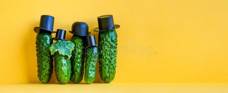 Komische grüne Gurkenfamilie auf gelbem Hintergrund Fünf lustiges Gemüse mit schwarzen altmodischen Hüten kreativ lizenzfreie stockfotos