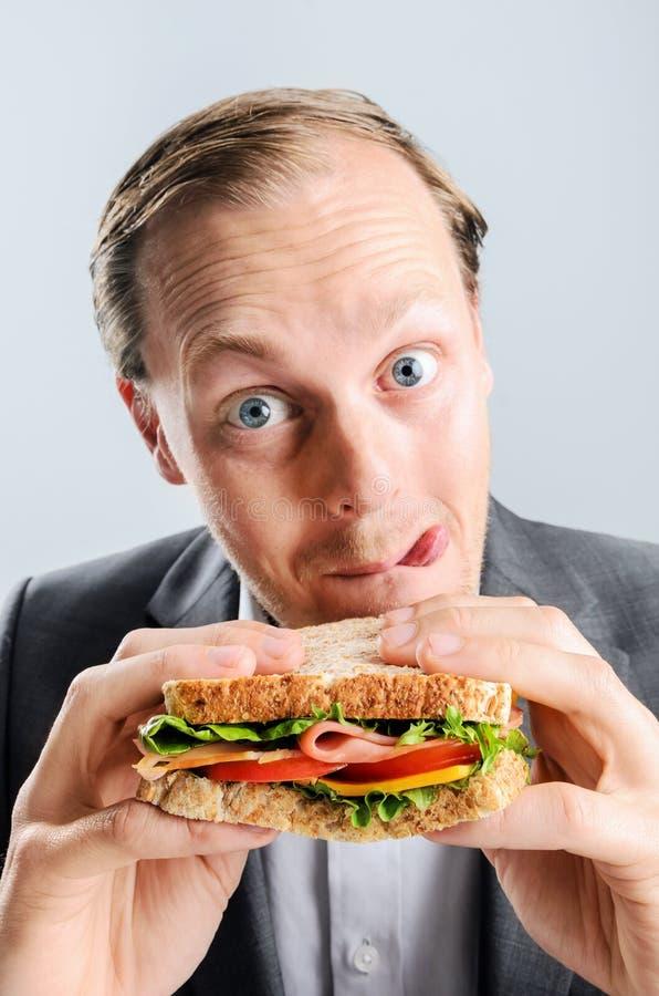 Komische mens die sandwich met grappige uitdrukking eten stock afbeeldingen