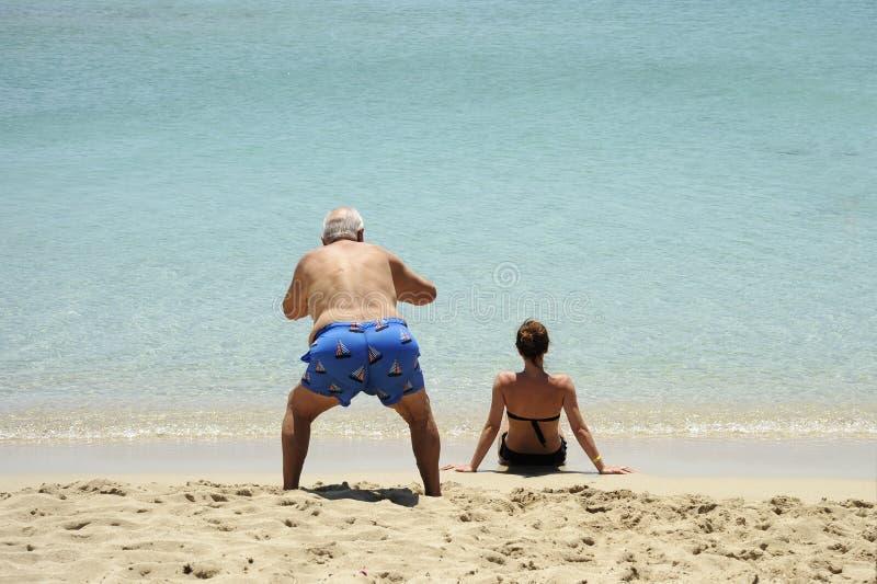 Komische und lustige Situation Ein älterer Mann macht Fotos der hinteren Ansicht des schönen Mädchens sitzend auf dem Strand stockbilder