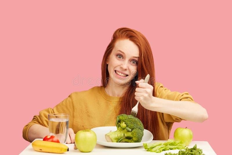Komisk grimacing rolig kvinna på sund mat som äter med broccoli och grönsaker arkivbild