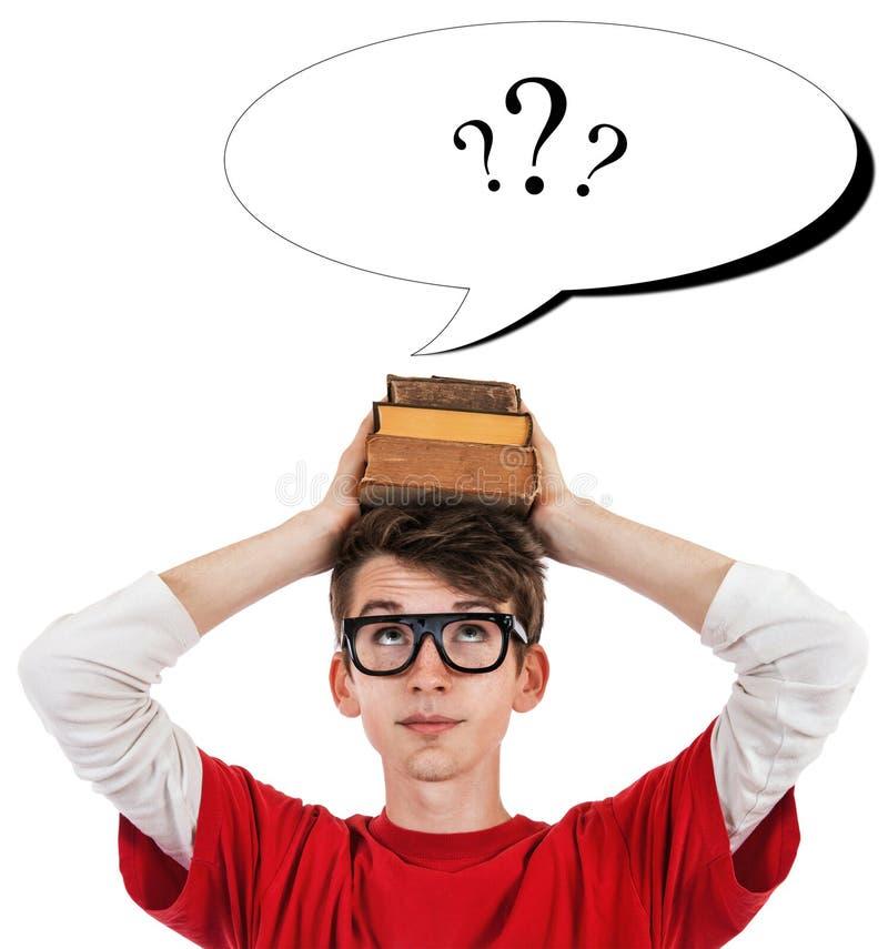 Komiskt skolpojkefoto med böcker på huvud- och frågefläckarna i anförandeballong arkivfoto