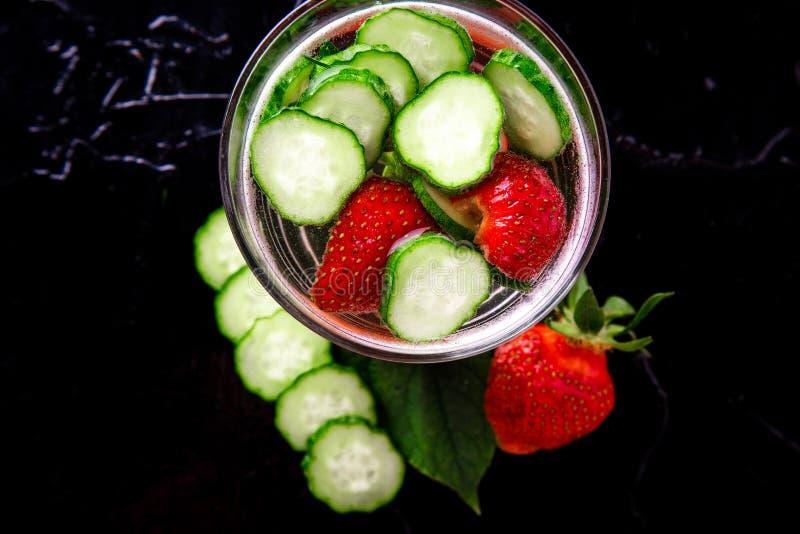 Komkommer en aardbei detox water in glas op zwarte achtergrond Dieet Hoogste mening stock afbeeldingen