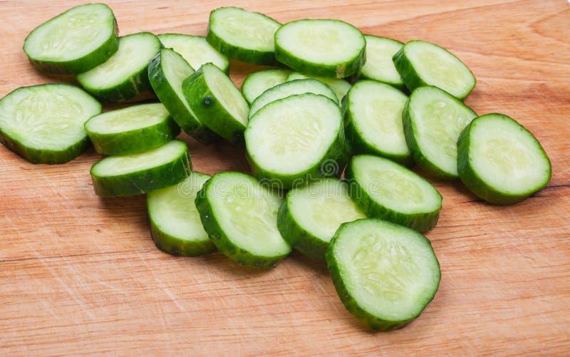 Komkommer op een houten raad wordt gesneden die stock foto's