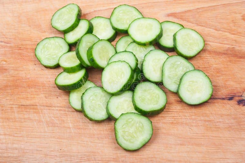 Komkommer op een houten raad wordt gesneden die stock afbeelding