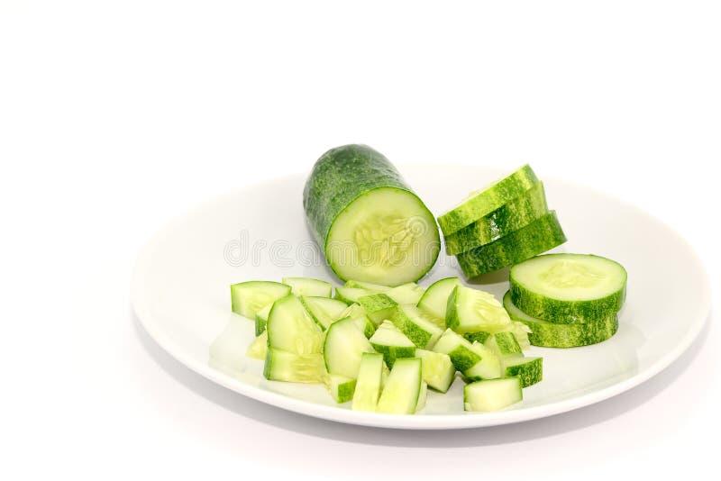 Komkommers die op Witte Plaat worden gesneden stock afbeelding