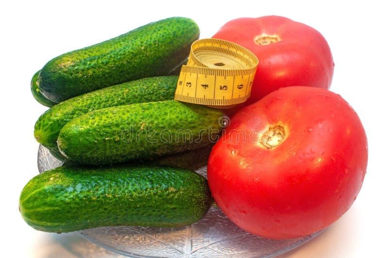 Komkommers met tomaten en het meten van band in een plaat royalty-vrije stock fotografie