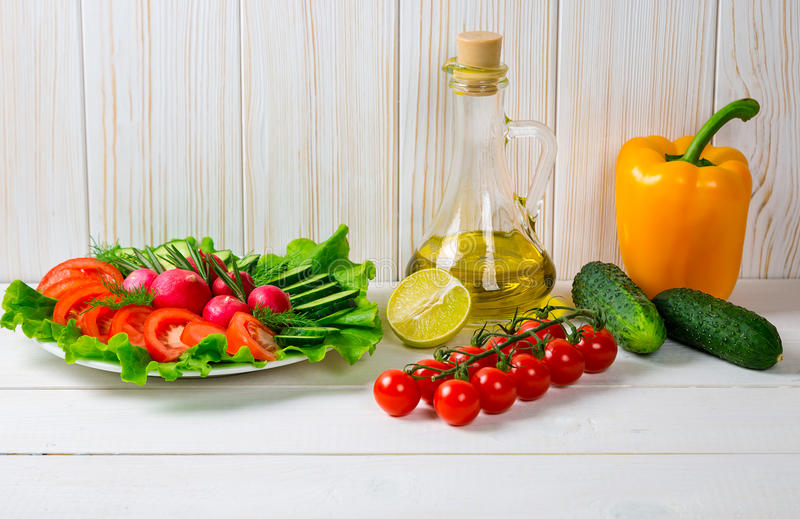 Komkommers, radijs, tomatenkers, olijfolie, kruid en kruiden op oude witte houten achtergrond royalty-vrije stock fotografie