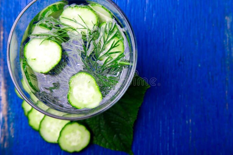 Komkommerwater in glas met dille op blauwe houten achtergrond Detox, dieet Hoogste mening De ruimte van het exemplaar stock foto's