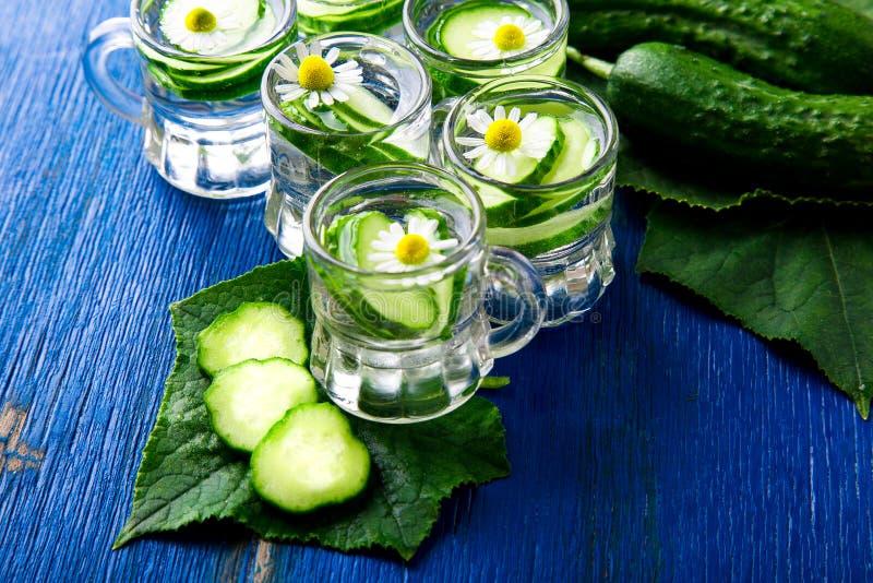 Komkommerwater in zes de kleine kruik van het metselaarglas op blauwe achtergrond rustic detox stock foto's