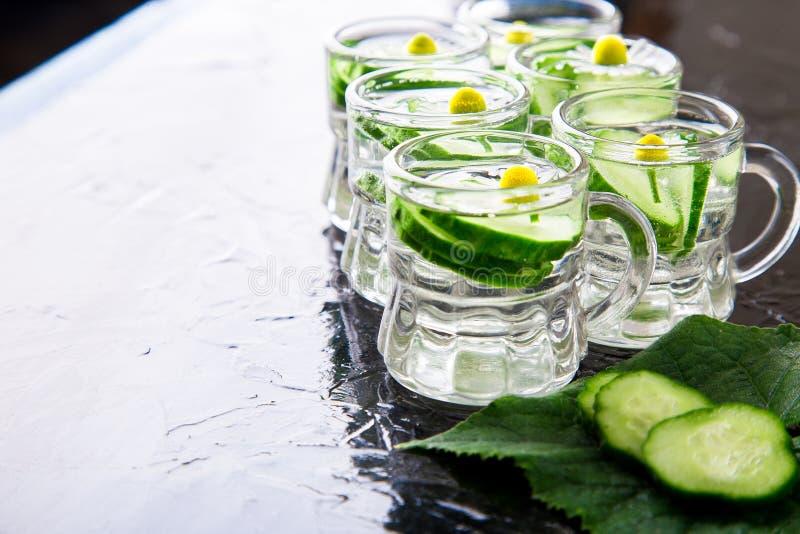 Komkommerwater in zes de kleine kruik van het metselaarglas op zwarte achtergrond stock afbeeldingen