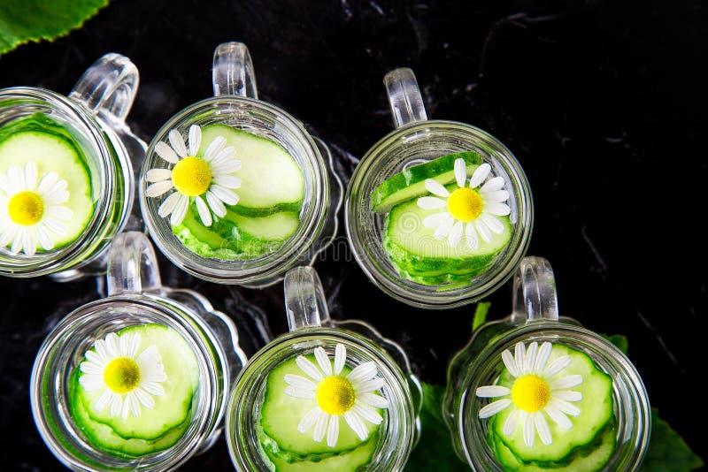 Komkommerwater in zes de kleine kruik van het metselaarglas op zwarte achtergrond Hoogste mening stock foto's