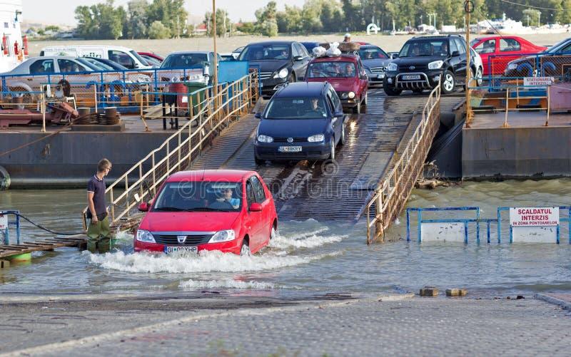 Kommande down för bilar från färjatransporten över den översvämmade Donauen royaltyfria bilder