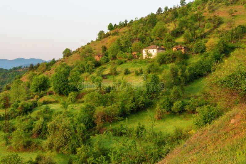 kommande fjäder Fantastisk vårsikt med lite byn i Rhodopi berg, Bulgarien arkivfoto